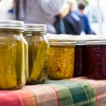 Jars of homemade corn relish and pickled cucumbers by Growing Sp